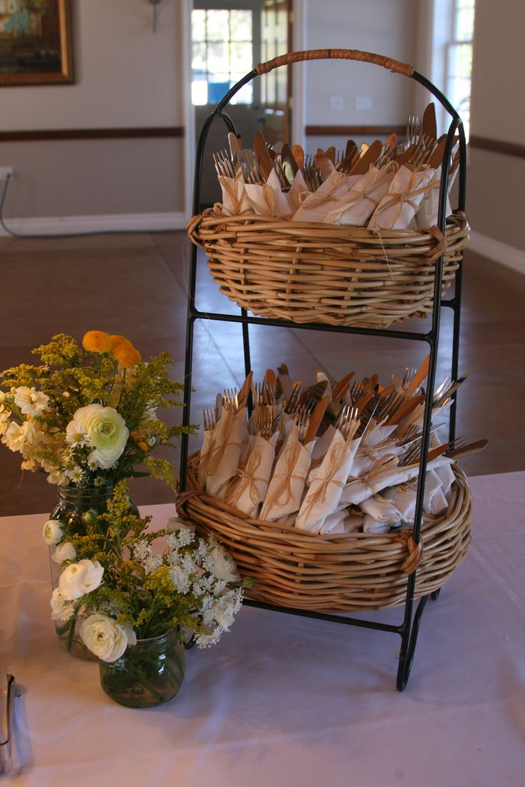 another inexpensive way to wrap utensils in napkins in this two tiered basket on buffet table