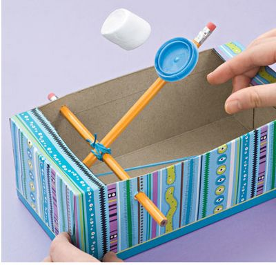 Marshmallow catapult using a tissue box, rubber bands, pencil and a milk lid