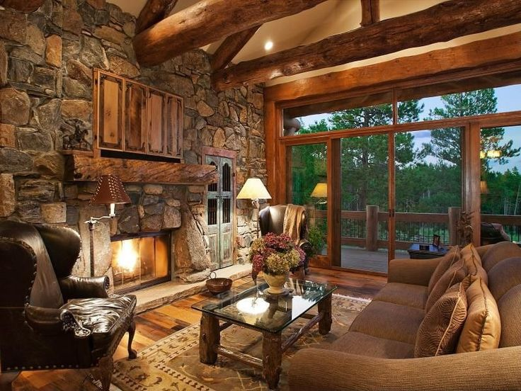 A large glass sliding door gives a great view of the outdoors from this stunning rustic living room. The space is dominated by a fireplace incorporated into a full height stone wall.