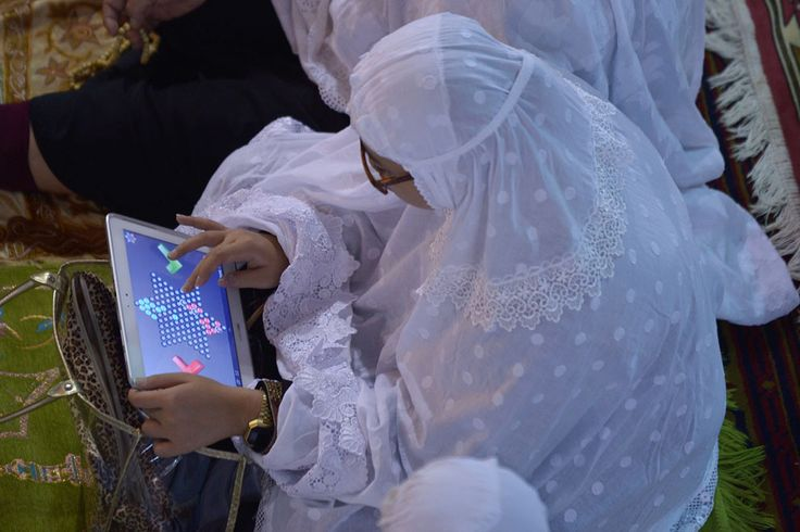 An Indonesian woman plays a game on her tablet during a sermon on the first night of Ramadan at the Istiqlal mosque in Jakarta, on July 9, 2013  | AFP/Getty Images | © Adek Berry