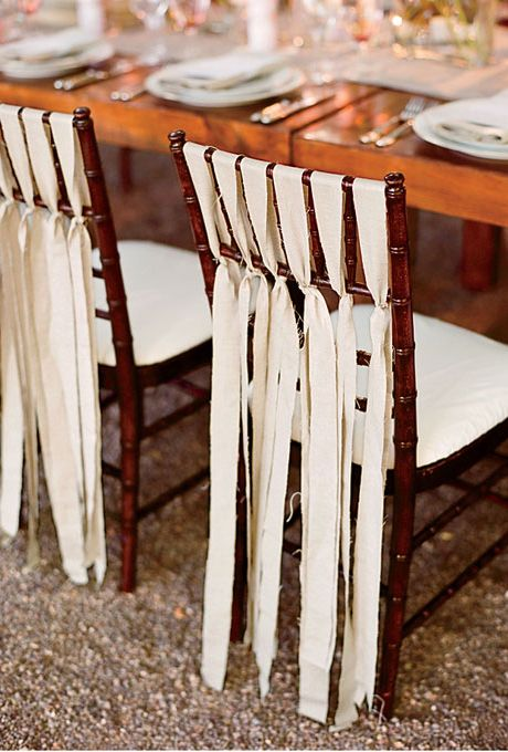 Chairs decorated with ribbon at wedding reception The bride cut linen fabric