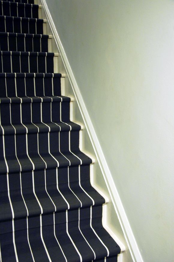 When it comes time to replace the carpet on my stairs I'm totally doing this! She used runners from Ikea, painted the edges white, and secured it all with a nail gun.  So much more character than carpet!  from Little Green Notebook: DIY: Stair Runner