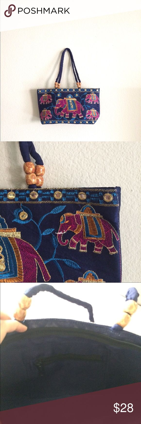 Handmade, embroidered ethnic handbag This little cloth handbag from India is handmade, beautifully embroidered, fully lined and adorned with sequin work on the body and wooden beads on the handles. The ethnic look is unmistakable. A beautiful melange of colors complement the look of this bag. The main closure is zippered (pic 3) and There is one zippered compartment on the inside of the bag as well (pic 4). Handmade Bags