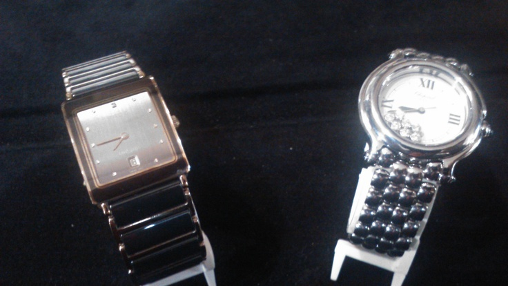 A high quality unisex Rado tank watch, with Swiss watch movement, rendered in black bordered in gold upon the left, alongside a unique look in a ladies' Chopard wristwatch with floating diamonds adorning the dial.