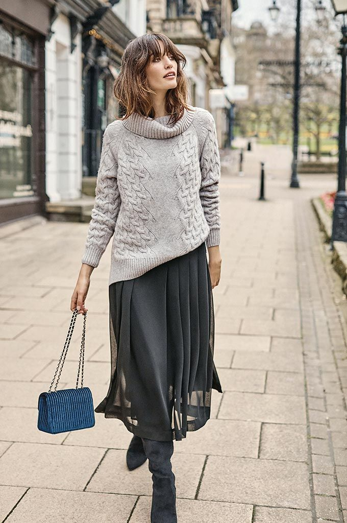 e4c3a7f0dd A stylish woman walking down the street in a grey knitted sweater, a black  maxi skirt and suede black slouch boots. Image by Pure Collection.