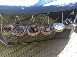 """Pre-School Play store their loose parts in slightly-smaller-than-normal hanging baskets... they are filled with sticks, pebbles, fir cones, tree blocks, white pebbles & some of their small world insects & fairies ("""",)"""