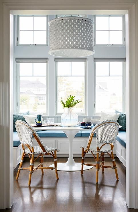 Arteriors Jarrod Wood Pendant hangs over a U-shaped dining banquette accented with white shiplap trim and blue cushions facing an oval Saarinen Dining Table and French bistro chairs.