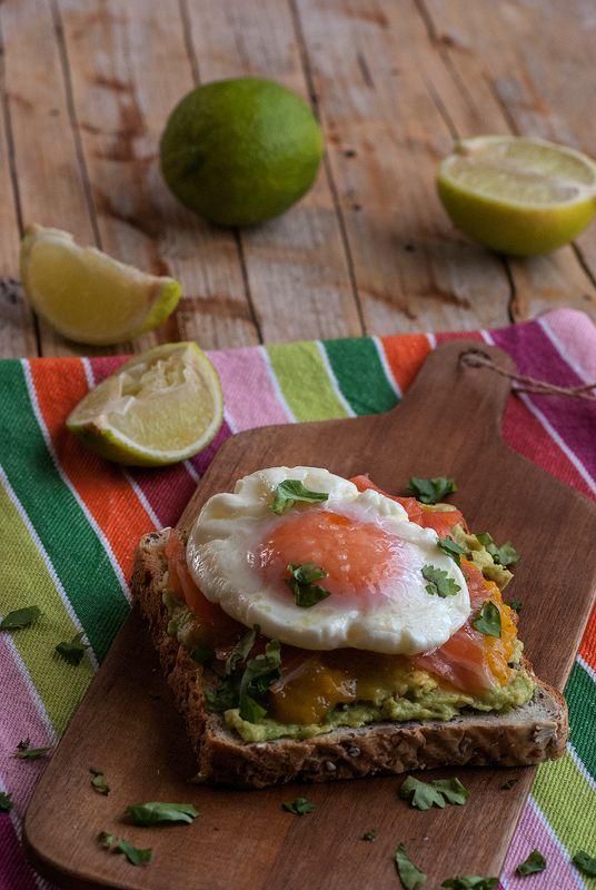 huevo escalfado sobre tosta con aguacate mango espaciado y salmón