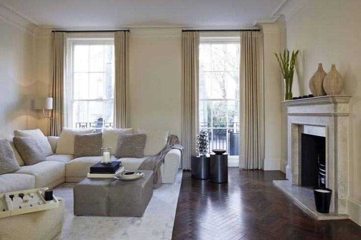 Cream and champagne decor, floor-to-ceiling windows, and polished parquet flooring keep the living room clean, bright, and homey.  Photo courtesy of Lawson Robb