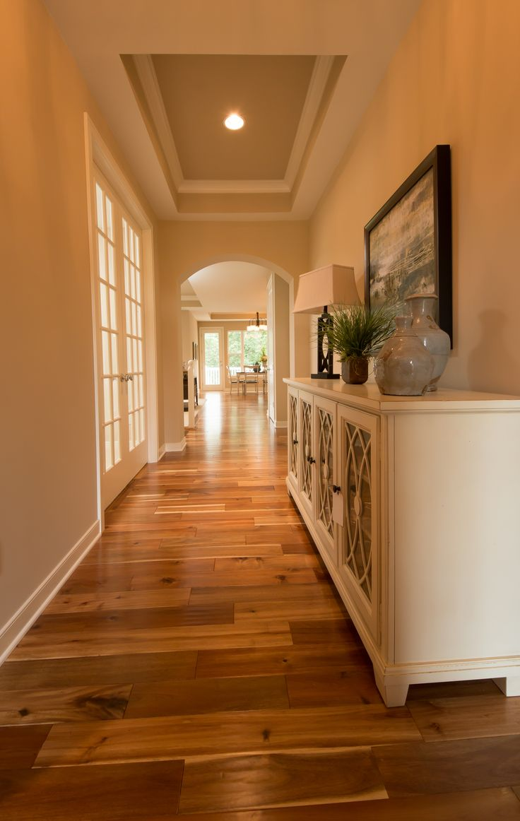 Acacia hardwood flooring, painted coffer ceiling with crown molding, access to the kitchen and living room through an arched opening.