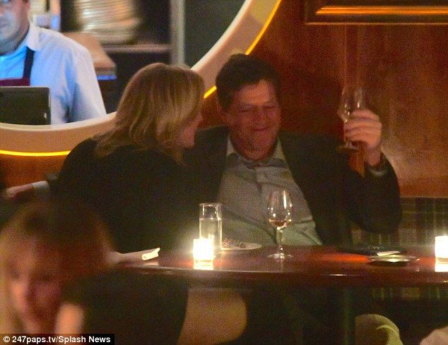 Laracozied up to her date once they were seated at the table, putting her arm around the ...