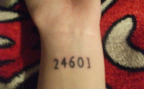 This is what I'm thinking about. Slightly different font, and a small open handcuff on each side (so it will look symbolic and less like an actual prison number) I thought about a candlestick with it but I don't think it would look good