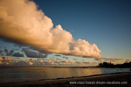 Beautiful clouds painted by the yellow teint of the sunset light. Spreckelsville Beach, Maui Hawaii.