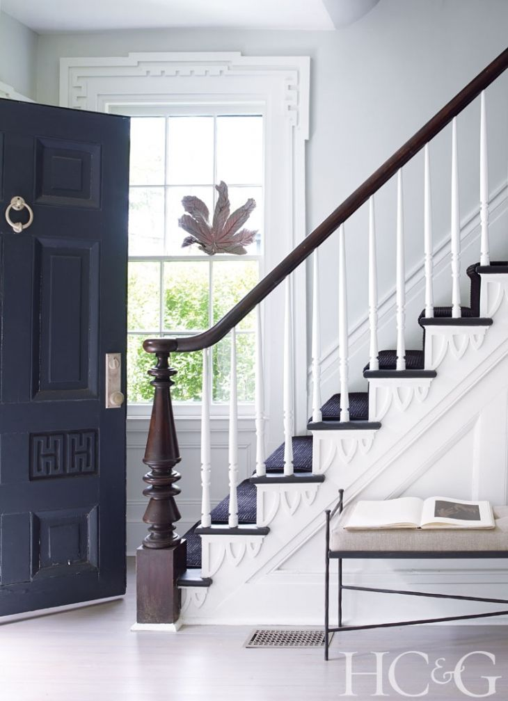 The entry features original Greek Revival molding around the window. The custom iron bench is from Ruby Beets.
