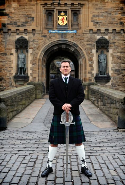 """Bruce Campbell holding Connor Macleod's Highlander Broadsword in Clan Campbell tartan dress in front statues of Robert the Bruce and William """"Braveheart"""" Wallace at Edinbrugh Castle in Edinburgh, Scotland, UK."""