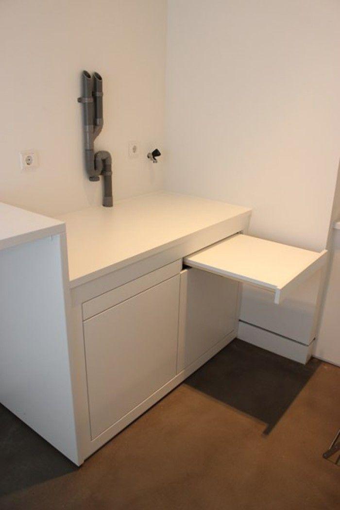 door meubelmaker gemaakt voor wasmachine en droger, plek voor wasmanden en opbergruimte