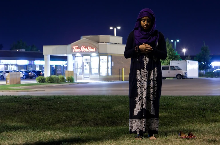 A Canadian Muslim woman stands in prayer near the national coffee chain Tim Hortons in Toronto, Ontario at the end of Ramadan. (© Yasin Dusoruth)