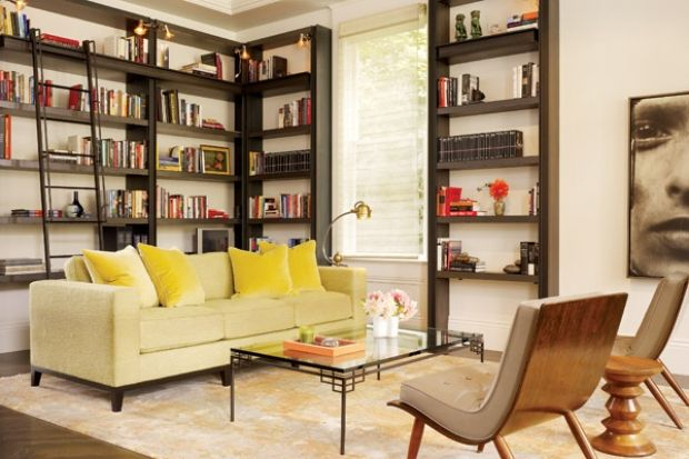 The dark wood floor dramatizes the wool and silk texture of the custom yellow, grey, taupe and cream mid-century modern rug. The yellow pillows pop of the pale green sofa. The rounded contours of the sofa and mid century chairs balance the angular lines of the book cases in this living room by Redmond Aldrich Design. Image courtesy California Home and Design Magazine.