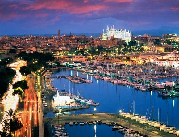 Palma de Mallorca, Spain. Poised on a sea wall above the marina, the city's massive gothic cathedral lights up the Spanish skyline.