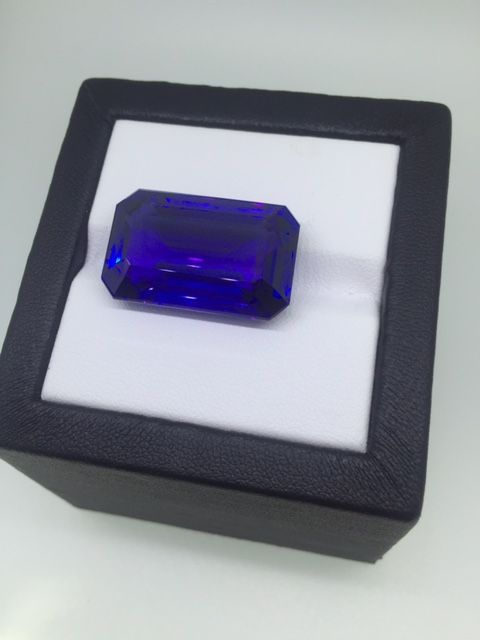 "35 carat tanzanite gemstone in an ""emerald cut"". The unique look of the emerald cut tanzanite  is created by the step cuts of its pavilion and its large, open table. The shape was originally developed for the cutting of emeralds, thus the name.  While less fiery than a more common round or oval brilliant cut, the long lines and dramatic flashes of light give the emerald cut an elegant appeal."