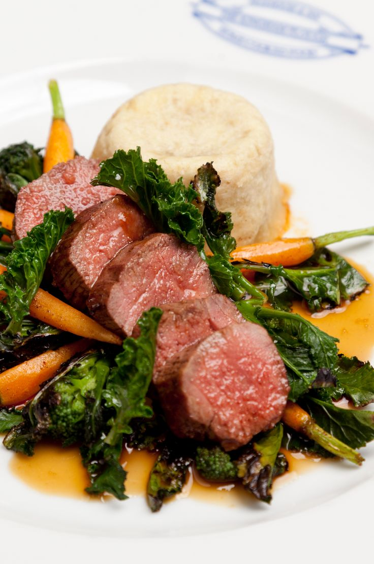 Emily Watkins' lamb loin with pudding recipe celebrates the flavours and ingredients of spring, featuring seasonal purple sprouting broccoli alongside lamb and carrots.