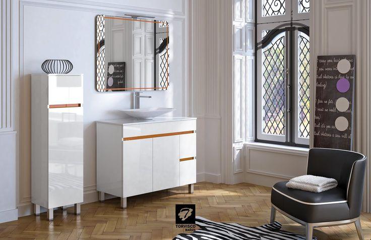 Mueble de baño SIL de 100 cms en  blanco brillo con tapa MOONSTONE y lavabo SOFT. Espejo MARES en naranja, a conjunto con el detalle de los tiradores del mueble. Columna auxiliar de 35cms y foco ERIC. El KIT COLOR de los muebles puede elegirse en blanco, negro, wengué, chocolate, morado, azul, naranja, pistacho o rojo. Del catálogo BATHONE de TORVISCO GROUP.
