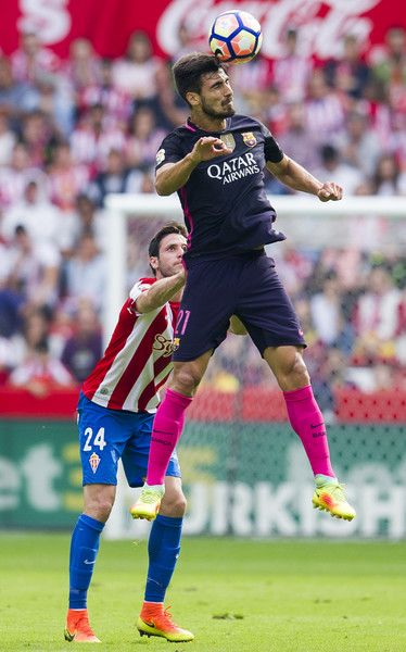 Andre Gomes of FC Barcelona duels for the ball with Duje Cop of Real Sporting de Gijon during the La Liga match between Real Sporting de Gijon and FC Barcelona at Estadio El Molinon on September 24, 2016 in Gijon, Spain.