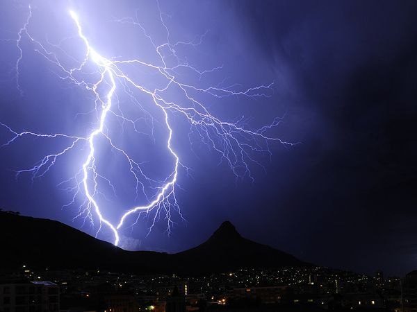 lightning forks and rejoins itself over table mountain and lion's head in cape town, south africa.