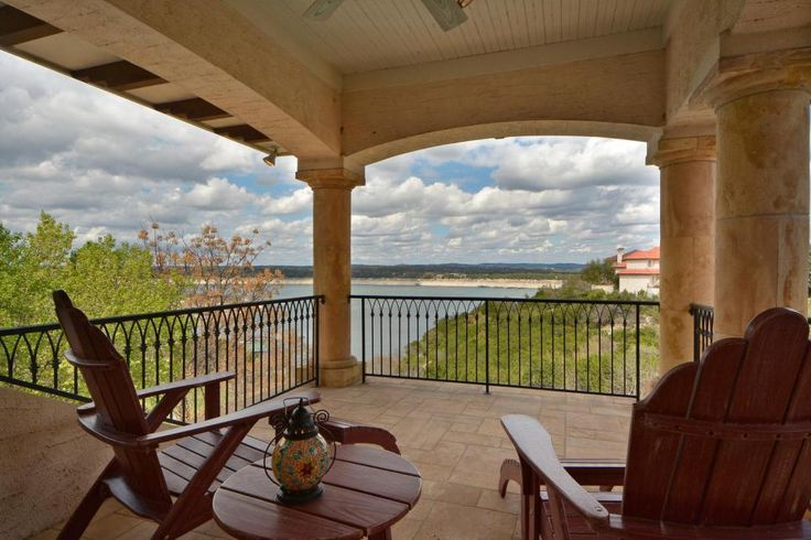 Two Adirondack chairs are positioned toward the gorgeous lake view from this balcony, another one of the home's impressive outdoor living areas. Stately columns and a wrought iron railing keep with the home's Mediterranean design.