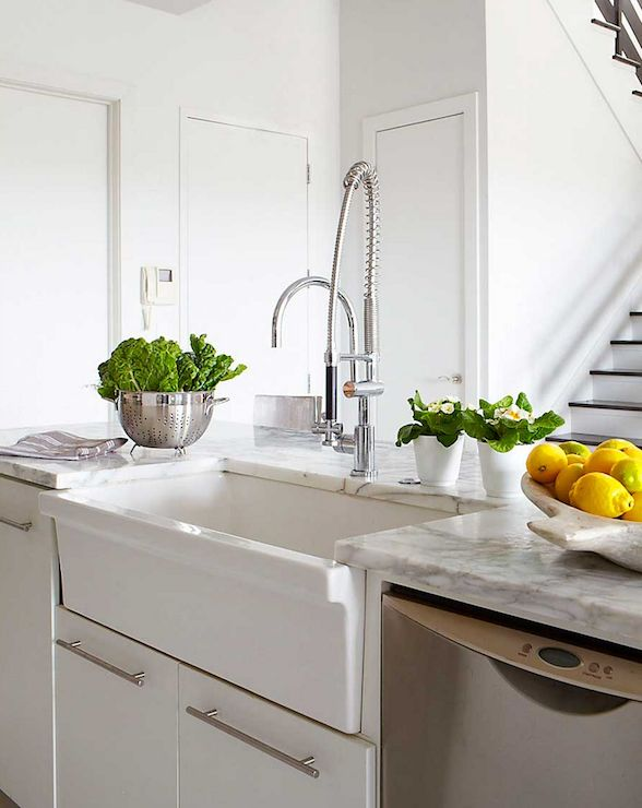 White kitchen island topped with white and gray marble with apron sink paired with spray faucet situated next to stainless steel dishwasher.