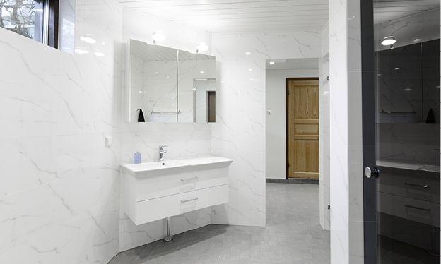 Kylpy- ja saunaosasto. Tässä kohteessa remontoitiin kylpyhuone, wc, sauna ja kodinhoitohuoneen lattia. Saunaosastosta haluttiin selkeä, tilavan oloinen ja valoisa. Kylpyhuone ja wc laatoitettiin samalla seinälaatalla. Kaikissa tiloissa käytettiin samaa lattialaattaa, jolloin tiloihin saatiin yhtenäinen linja. Saunaan ja wc-tilaan hankittiin lasiset ovet, näin valo pääsee joka suuntaan.