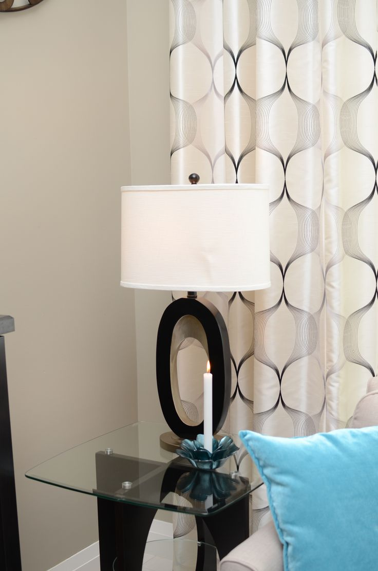 Living room end table with table lamp, candle and long curtains behind.
