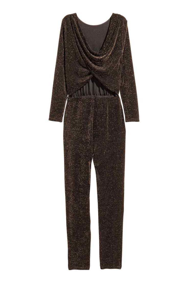 Glitterende jumpsuit: Een jumpsuit van tricot met glitters. Het model heeft lange mouwen, een gedrapeerde ruguitsnijding, elastiek in de taille met een cut-out erboven aan de achterkant en taps toelopende pijpen. Het lijfje is gevoerd.