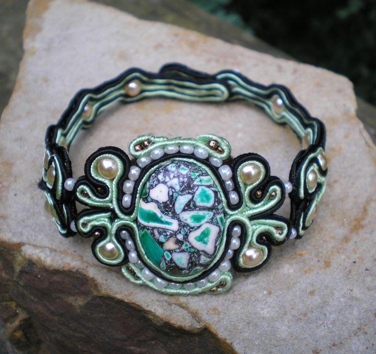 Jako z malachitu... Sutaškový náramekladěný do zelenočerného tónu. Centrální velký korálek, krémové perličky a rokajl zapracované do světle zeleného a černého sutaškového prýmku. Průměr náramku 6,5 cm, délka rozepnutého náramku je20 cm. Posunutím zapínání o 1 perličku se nechá ještě o 1,5 cm zvětšit.