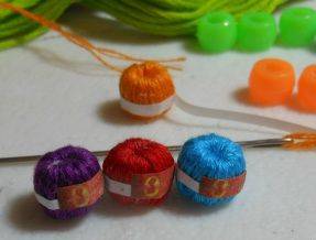 miniature balls of thread with help of kids plastic pearls
