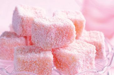 Pink lamingtons (squares of sponge cake dipped in frosting, then ...