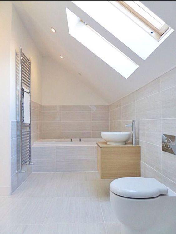 window on angled ceiling. Neutral beige bathroom, fully tiled around bath: