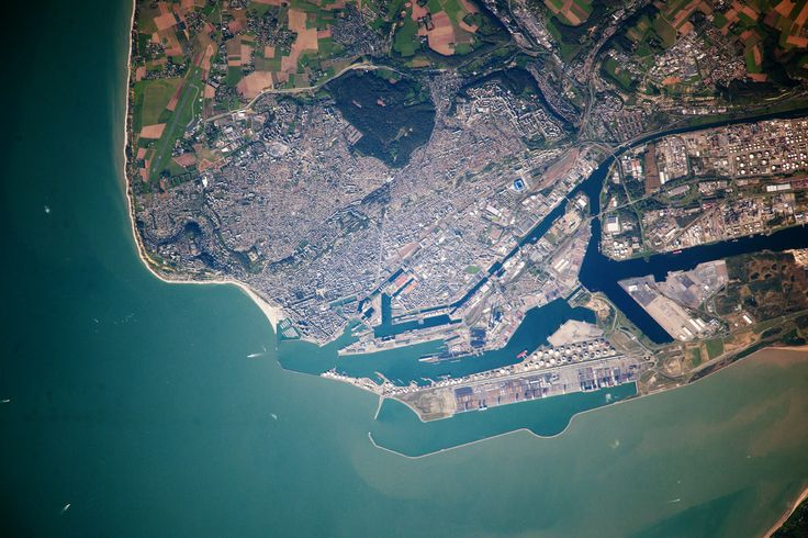 The port city of Le Havre sits at the confluence of the Seine River and the English Channel along the northern coastline of France (Upper Normandy region). It is the largest container port in France, and the second largest in total traffic after Marseille. The extensive port facilities, visible at image center, include numerous docks (large cargo ships are clearly visible), storage tanks for petroleum and other chemicals, and large industrial and warehouse facilities with white rooftops.