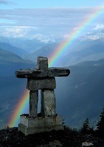 Rainbow beyond the crafted rocks of the mountain. Inukshuk, by edojan.