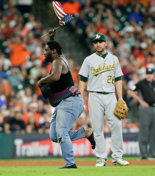 Danny Valencia Photos - A man runs past Danny Valencia #26 of the Oakland Athleticsonto the field in the fourth inning during a baseball game between the Oakland Athletics and Houston Astros at Minute Maid Park on June 4, 2016 in Houston, Texas. - Oakland Athletics v Houston Astros