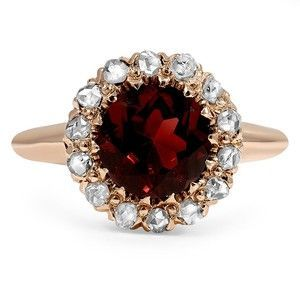 A captivating red garnet sits at the center of this Art Deco engagement ring in a feminine rose gold setting.