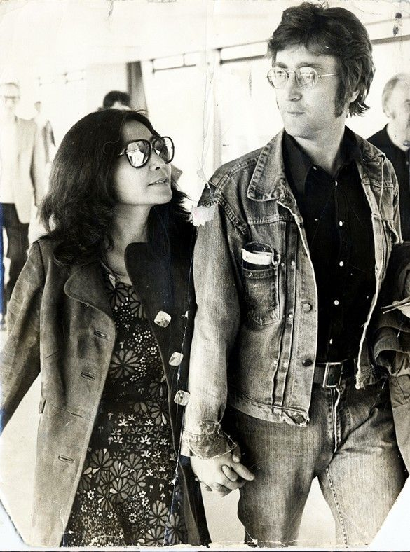 Yoko Ono wears a floral dress with a suede jacket and mirrored sunglasses. John Lennon wears a button-down shirt with a denim jacket, belted jeans, and round sunglasses