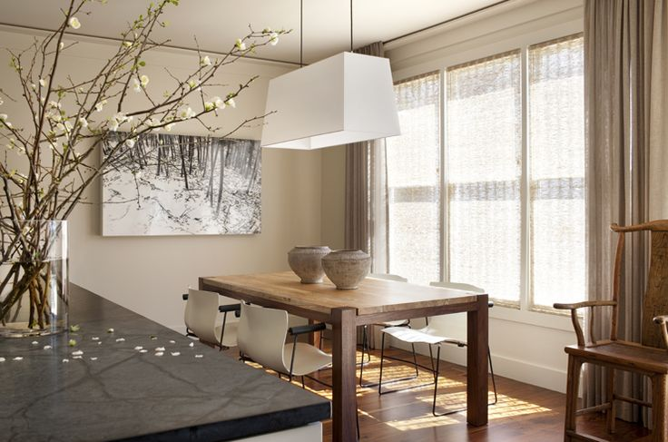 Beautiful white tapered pendant chandelier, rustic table with white modern chairs, modern art piece, love the blossom branch arrangement