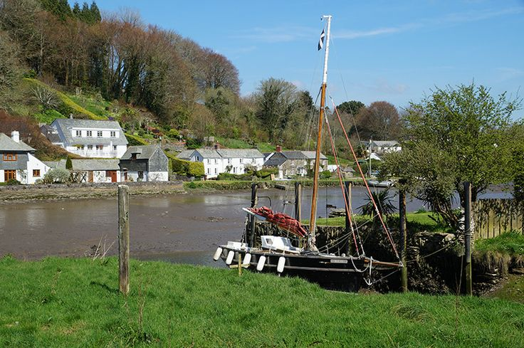 Cornish slate cottages and a sailing boat at a small private dock on Lerryn Creek