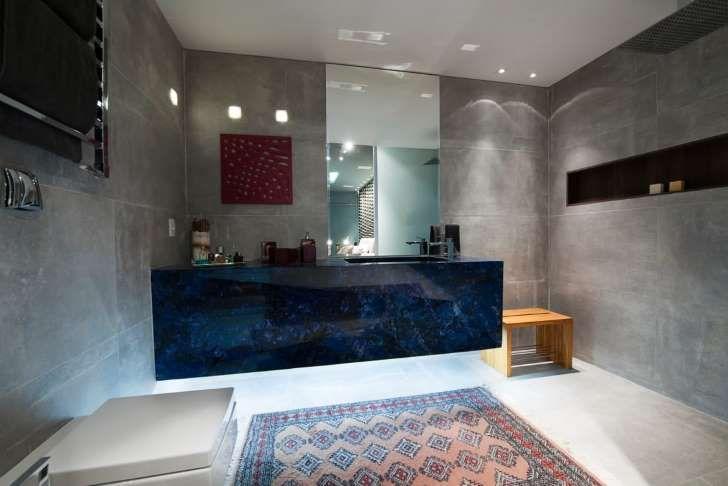 El baño es otro lujo. El mueble en el que se ubica el lavamanos es una belleza. El color azul obscuro aporta un aire sofisticado y creativo. Los revestimientos, en gris, en las paredes y el diseño de iluminación añaden una nota muy industrial. El nicho alargado en la pared no sólo aporta funcionalidad también es un elemento estético muy contemporáneo.