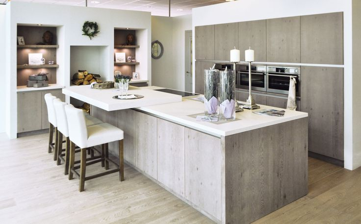 Landelijke keuken met eiken afwerking.  Deze landelijke keuken geeft je direct een warm gevoel door de eiken afwerking en de houtblokken. De keuken is voorzien van ingewerkte kolomkasten en ingebouwde keukentoestellen. Het kookeiland is in bezit van alle nodige toestellen en kasten. Aan het eiland is ook een toog gemaakt waar aan gegeten kan worden. De verlichting, de lichtgrijze kleur op de muren en het werkblad zorgen voor een licht effect dat eveneens ruimte creëert.