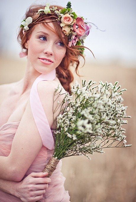 Secured with a simple pink ribbon, this eclectic flower crown, designed by Akiko Floral Artistry, includes real, lace, and artificial flowers as well as feathers. Combined with a loose, wavy braid, the look is perfect for a bride planning a rustic wedding with plenty of natural and handmade details.