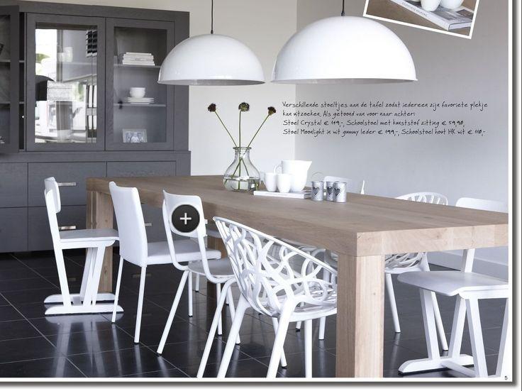Houten tafel met allemaal verschillende witte stoelen, leuk idee!