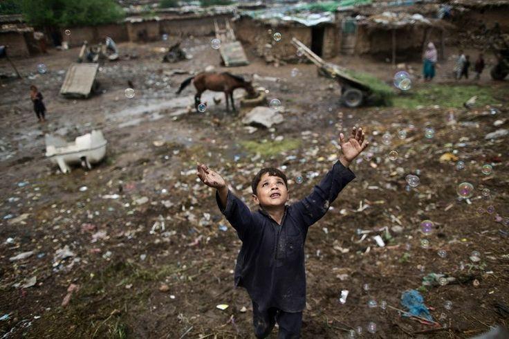 Islamabad. Un niño afgano persigue burbujas de jabón y juega con otros menores a las afueras de la capital de Pakistán, país que durante más...