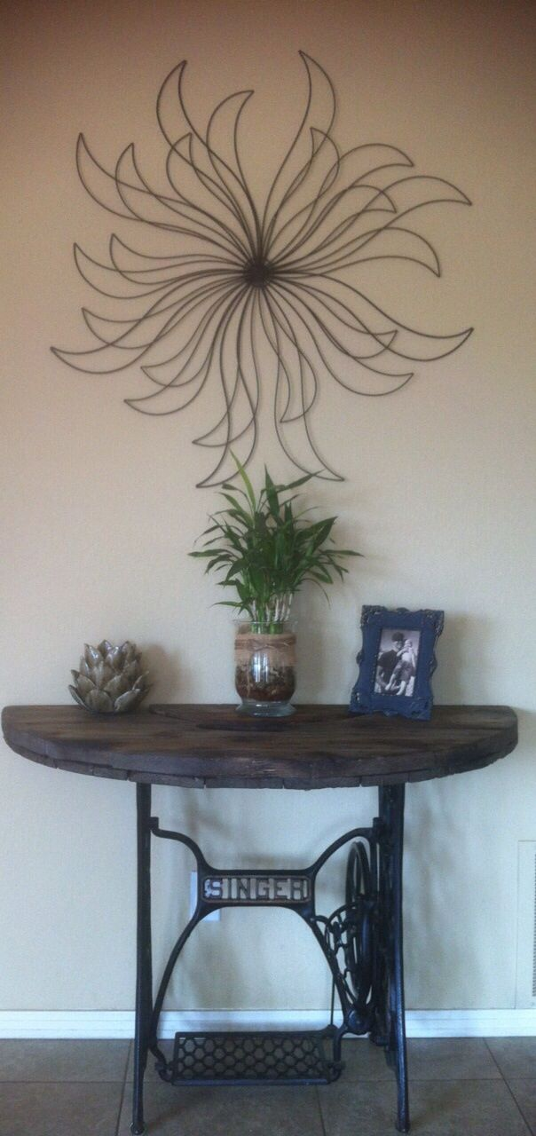 DIY foyer table used an old singer sewing machine base that is cast iron then cut an old wire spool top in half torched it to bring out the wood detail and added a couple burn marks for that old barn look then wax it.